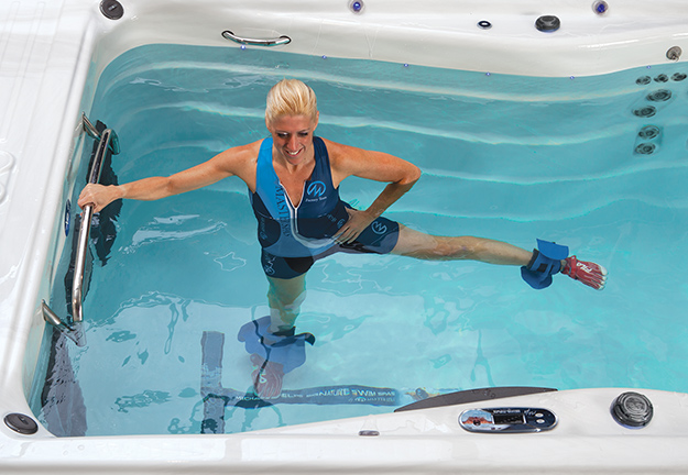 Woman exercising in a Michael Phelps Signature Series Swim Spa.