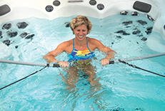 A woman exercising in a Michael Phelps Swim Spa by Master Spas