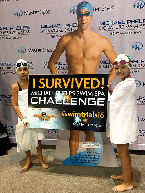 Two girls proudly show they survived the Michael Phelps Swim Spa Challenge